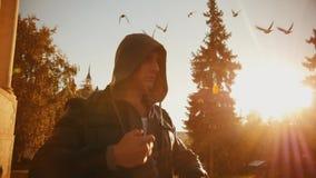 Ein junger grober Mann setzt an eine Haube, wenn Taube fliegen Fangen Sie an, im Fall auszubilden stock video
