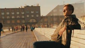 Ein junger grober Mann sitzt auf einer Bank und betrachtet Touristen stock video footage
