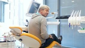 Ein junger gutaussehender Mann, der in einem Zahnarztstuhl sitzt, macht er, lächelt zu Kamera und zeigt sich einen Daumen stock footage