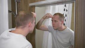 Ein junger gutaussehender Mann Der Mann sah Akne auf seiner Stirn im Spiegel Ein Mann umfasst Akne mit einem Abdeckstift Zeitlupe stock footage