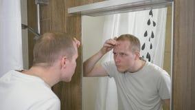 Ein junger gutaussehender Mann Der Mann sah Akne auf seiner Stirn im Spiegel Zeitlupe 4k stock footage