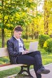 Ein junger gutaussehender Mann ist, arbeitend sitzend und im Park mit einem Laptop Der Kerlfreiberufler arbeitet draußen Lizenzfreies Stockfoto