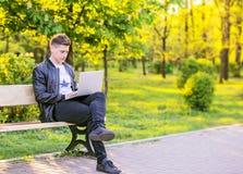 Ein junger gutaussehender Mann ist, arbeitend sitzend und im Park mit einem Laptop Der Kerlfreiberufler arbeitet draußen Lizenzfreie Stockfotos