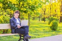 Ein junger gutaussehender Mann ist, arbeitend sitzend und im Park mit einem Laptop Der Kerlfreiberufler arbeitet draußen Stockfotografie