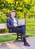 Ein junger gutaussehender Mann ist, arbeitend sitzend und im Park mit einem Laptop Der Kerlfreiberufler arbeitet draußen Lizenzfreie Stockbilder