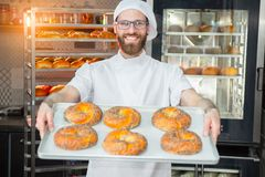 Ein junger hübscher Bäcker, der frische Bagel mit Mohn auf einem Behälter auf dem Hintergrund eines Ofens und des Gestells mit Ba stockbild