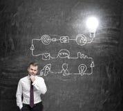 Ein junger hübscher Geschäftsmann denkt an den Prozess des Entwickelns einer neuen Idee Ein Flussdiagramm wird auf die schwarze T Stockfotos