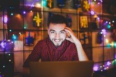 Ein junger hübscher kaukasischer Mann mit Bart und toothy Lächeln in einem roten karierten Hemd arbeitet hinter einem grauen Lapt lizenzfreies stockbild