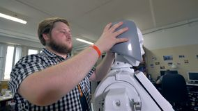 Ein junger Ingenieur überprüft wie Roboterplastikhaarsitz stock footage