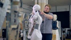 Ein junger Ingenieur baut einen Roboterkopf auseinander stock video