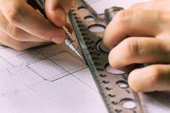 Ein junger Ingenieur lernt, mit Zeichnungen zu arbeiten lizenzfreie stockfotos