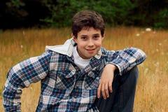 Ein junger jugendlicher Junge, der auf Gras kaut Stockfotografie