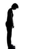 Ein junger Jugendlicher   trauriges Schauen des Mädchens hinunter Schattenbild Stockfoto