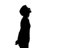 Ein junger Jugendlichjunge oder -mädchen, die oben Schattenbild schauen stockbild