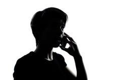 Ein junger Jugendlichjunge oder -mädchen am Telefon Stockbild