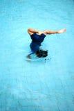Ein junger Junge, der einen Somersault im Swimmingpool tut Lizenzfreie Stockfotografie