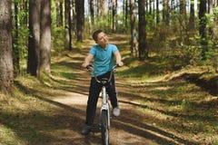 Ein junger kaukasischer Junge f?hrt Fahrrad an einem sonnigen Tag lizenzfreie stockfotos