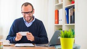 Ein junger kaukasischer Mann, der an einem Schreibtisch mit einem Laptop und einem Handy arbeitet. Stockfoto