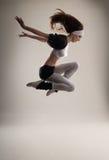 Ein junger kaukasischer weiblicher Tänzer in einem Sprung Lizenzfreies Stockfoto