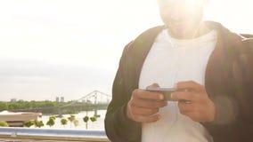 Ein junger Kerl benutzt seinen Handy stock video