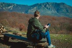Ein junger Kerl, der f?r das Wandern gekleidet wird, sitzt hoch in den Bergen und h?lt einen Handy stockbild