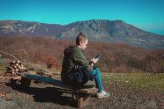 Ein junger Kerl, der für das Wandern gekleidet wird, sitzt hoch in den Bergen und schaut einen Handy stockbild