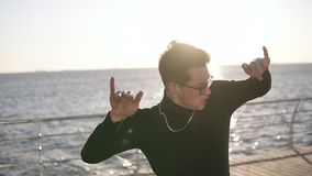Ein junger Kerl in einem schwarzen Blazer und in den Gläsern kam zur Küste, lässt seinen Mantel auf dem Boden fallen und begann z