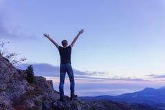 Ein junger Kerl in einem schwarzen Hemd steht auf einen Berg und verbreitet seine Arme in Richtung zum Himmel gegen den Hintergru lizenzfreies stockbild
