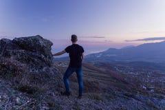 Ein junger Kerl in einem schwarzen T-Shirt steht auf einen Berg, mit seinem zurück zu der Kamera und starrt sunse an lizenzfreies stockbild