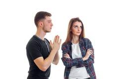 Ein junger Kerl in einem T-Shirt faltete die Palmen, die zusammen das Mädchen betrachten und bittet um Verzeihen Stockfoto