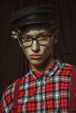 Ein junger Kerl in einer schwarzen Kappe, in den Gläsern und in den Blumen hinter seinem Ohr Stockfotografie