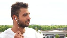 Ein junger Kerl hört auf etwas in seinen Kopfhörern und in Lachen stock video