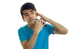 Ein junger Kerl im blauen Hemd rasiert sein Gesicht und blickt in Richtung Stockfoto