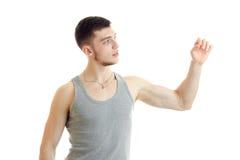 Ein junger Kerl im grauen Hemd blickt in Richtung der Erhöhungen seine Hand und belastenden Muskeln Lizenzfreie Stockfotografie