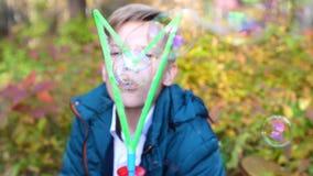 Ein junger Kerl im Park macht große Seifenblasen Feiertag und Unterhaltung im Freien stock video footage