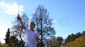 Ein junger Kerl im Park macht große Seifenblasen Feiertag und Unterhaltung im Freien stock footage