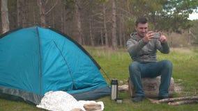 Ein junger Kerl sitzt auf einem großen Klotz nahe dem blauen Zelt und macht ein Foto am Telefon stock footage