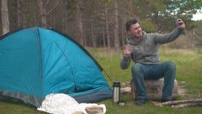 Ein junger Kerl sitzt auf einem großen Klotz nahe dem blauen Zelt und nimmt ein selfie am Telefon stock footage