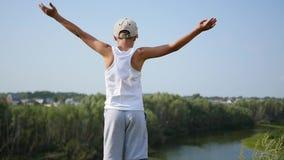 Ein junger Kerl steht auf der Flussbank Schöne Sommerlandschaft stock video footage