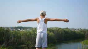 Ein junger Kerl steht auf der Flussbank Schöne Sommerlandschaft stock video