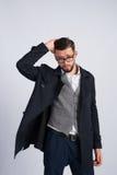 Ein junger Kerl steht in einem schwarzen Mantel Lizenzfreie Stockbilder