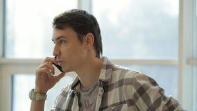 Ein junger kurzrasierter Mann in einem karierten Hemd sprechend auf Telefon und Blicken an der Uhr auf ihrem Arm stock video footage