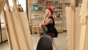 Ein junger lächelnder Blondinekünstler in ihrem Studio, das auf einem Stuhl sitzt stock footage