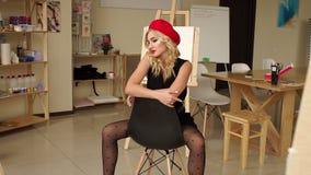 Ein junger lächelnder Blondinekünstler in ihrem Studio, das auf einem Stuhl sitzt stock video footage