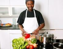Ein junger lächelnder Chef, der in der Küche kocht Stockfoto