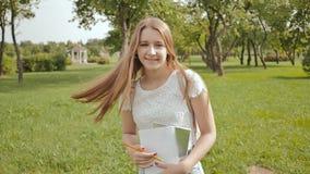 Ein junger Mädchenstudent mit einem Rucksack auf ihrem zurück und Anmerkungen in ihren Händen geht in den Park Rest während der S stock video