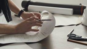 Ein junger männlicher Architekt arbeitet an dem Projekt von neuen Wohnungen Ehemann ist ein Architekt zeichnet einen Plan, Grafik stock footage