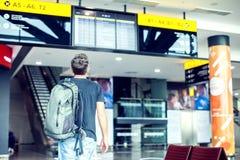 Ein junger männlicher Reisender mit einem Rucksack betrachtet die Informationen b lizenzfreie stockfotos