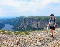 Ein junger männlicher Wanderer, der die großartigen Ansichten von auf Gros Morne Mountain in Gros Morne National Park, Neufundlan stockfotografie