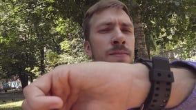 Ein junger Mann auf der Straße, die seine Uhr betrachtet stock footage